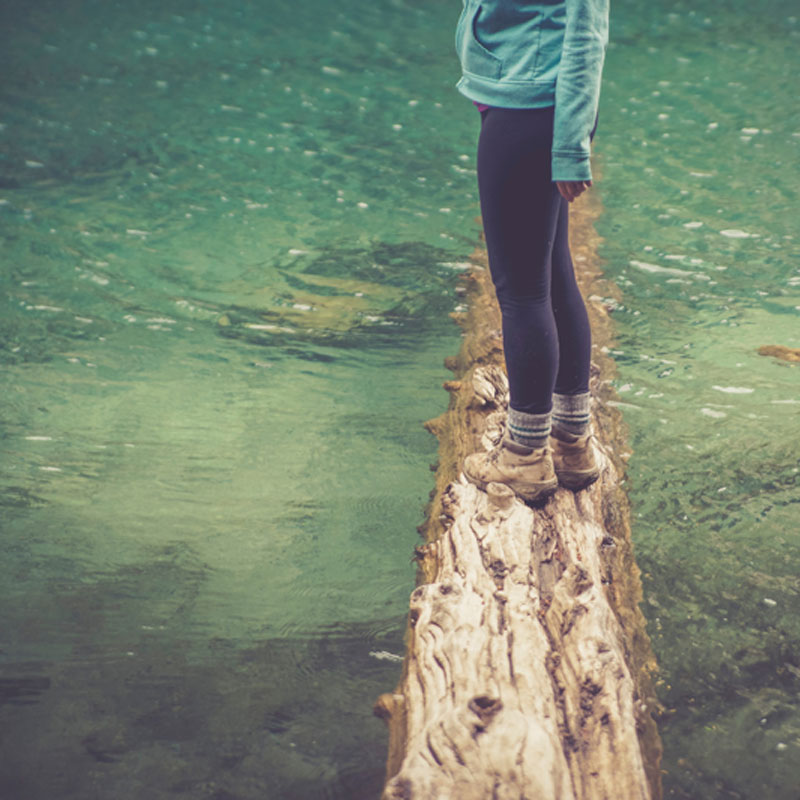 girl standing on a tree trunk