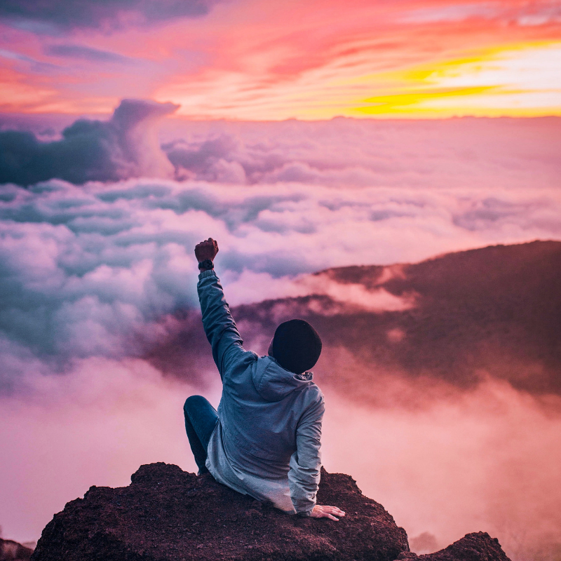 empowering guy on a mountain